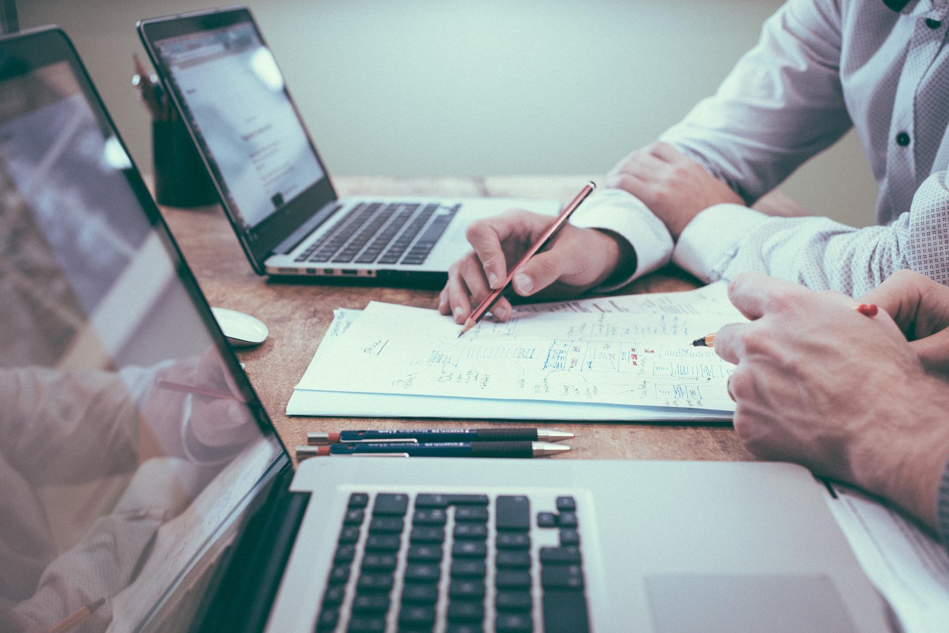 Dos personas trabajando con dos ordenadores y un papel